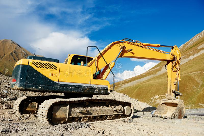 Excavator loader machine at mountain road construction site royalty free stock images