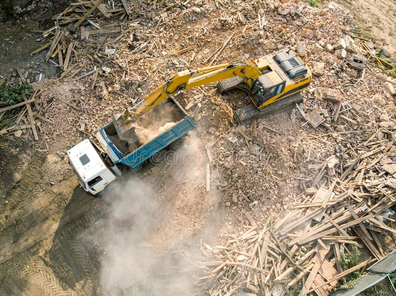 excavator loading debris of a destroyed building in truck. aerial view of demolition site royalty free stock image