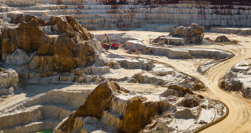 Excavator loading dump truck with raw kaolin in kaolin open pit mine stock photo