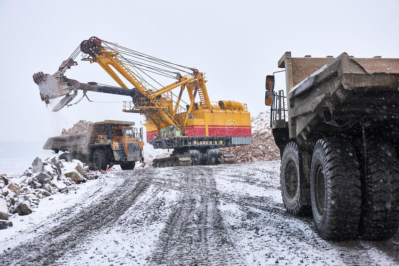 Excavator loading granite or ore into dump truck at opencast stock image