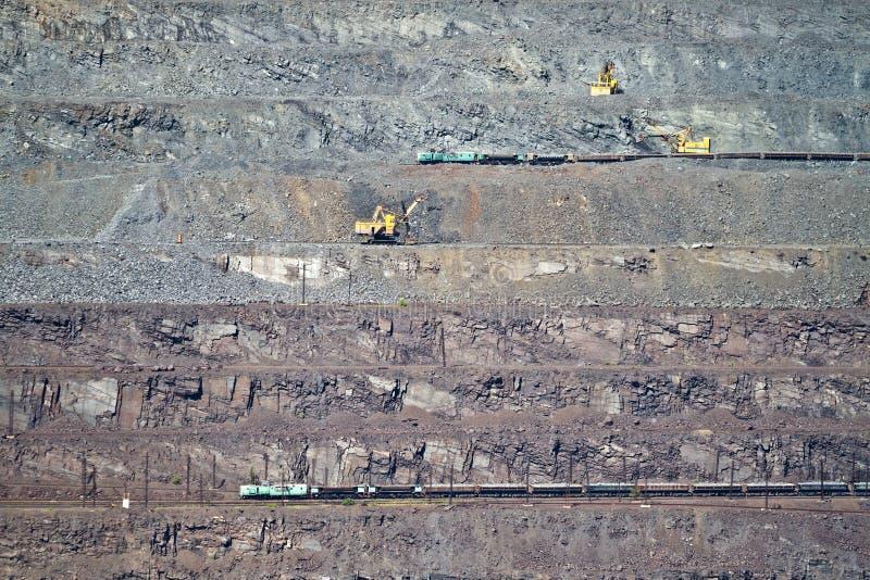 Excavator loading iron ore into goods wagon on the iron ore opencast mine royalty free stock image