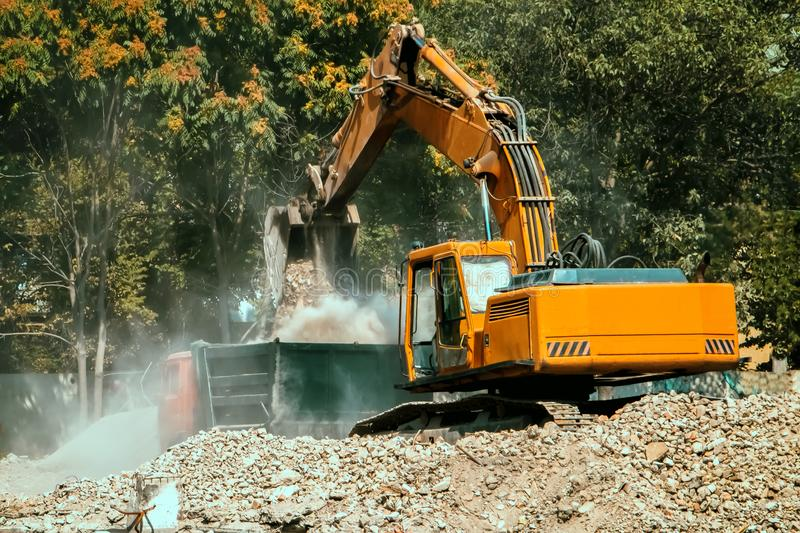 The excavator loads the dump truck with gravel. stock images