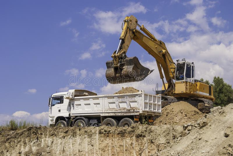 Excavator loads dump truck soil on the construction site.  royalty free stock image