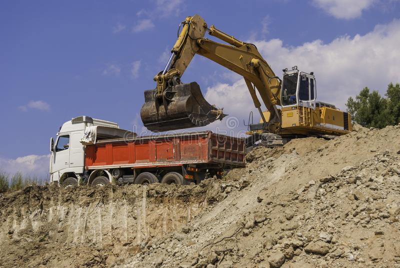 Excavator loads dump truck soil on the construction site.  royalty free stock photo