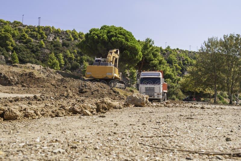 Excavator loads dump truck soil on the construction site.  stock photos
