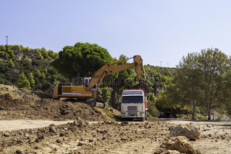 Excavator loads dump truck soil on the construction site.  stock image
