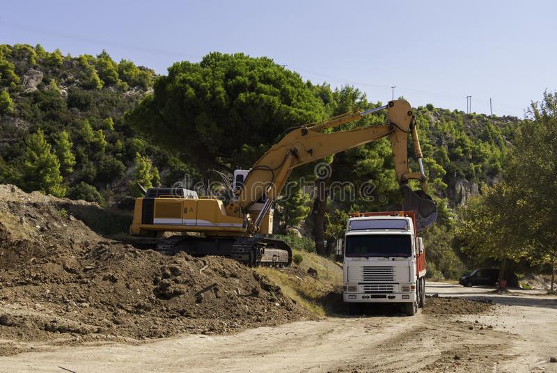 Excavator loads dump truck soil on the construction site.  royalty free stock photos