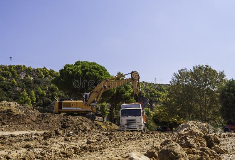 Excavator loads dump truck soil on the construction site.  stock photo