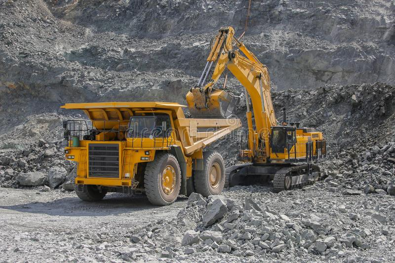 Excavator loads ore into a large mining dump truck royalty free stock photo
