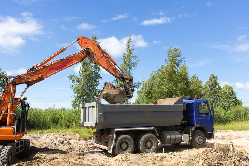 The excavator loads the tipper truck stock image