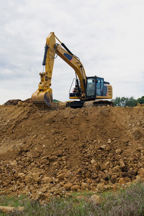 Excavator on large pile of dirt royalty free stock images