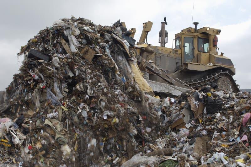 Excavator Moving Garbage. At dumping ground royalty free stock photos