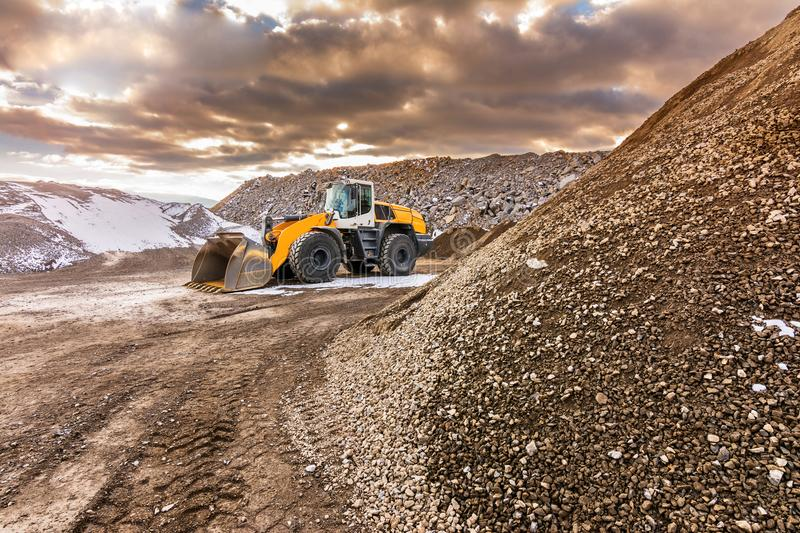 Excavator moving stone in an open pit mine in Spain. Mainly granite royalty free stock photography