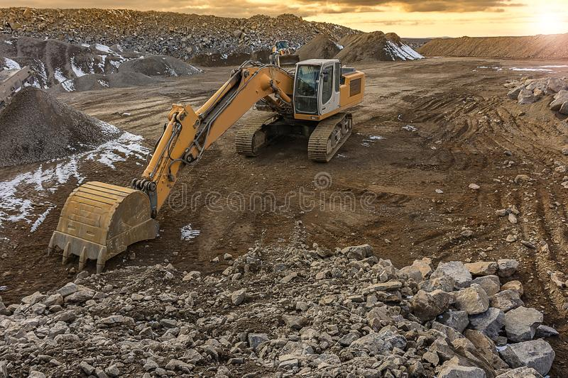 Excavator moving stone in an open pit mine in Spain. Mainly granite royalty free stock photos