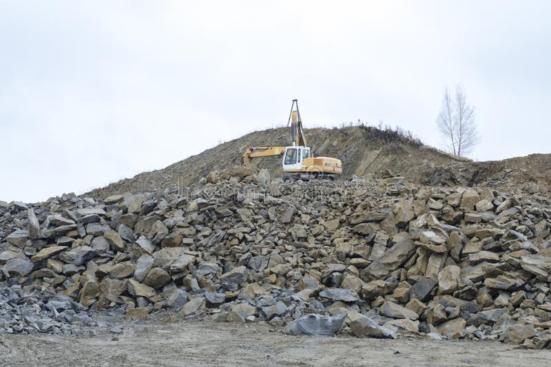 Excavator in an open pit mine stock images