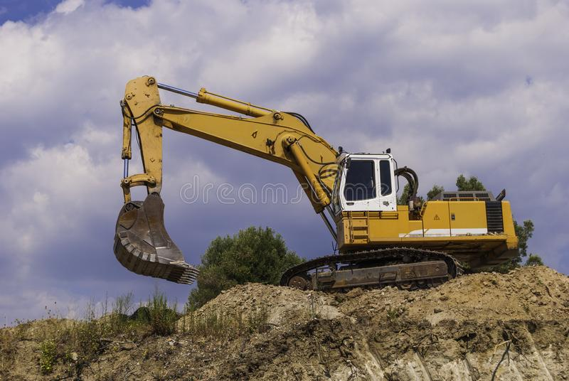 The excavator is preparing to load the dump truck with soil on the construction site.  royalty free stock photo