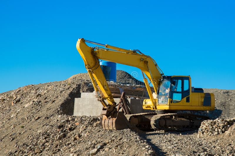 The excavator rakes in stones with his bucket. Excavator rakes rocky ground. Yellow excavator in work royalty free stock photography