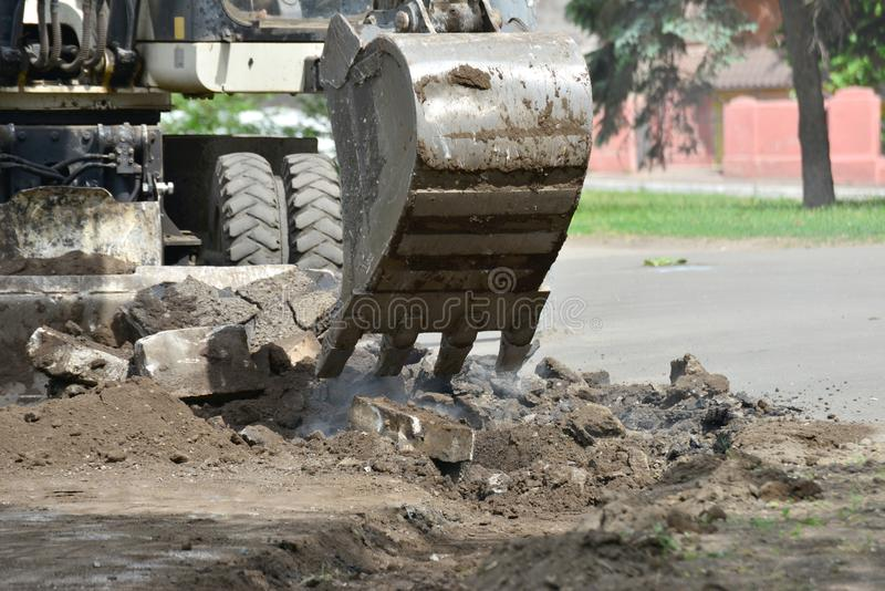 An excavator removes old asphalt for laying a new road royalty free stock photo