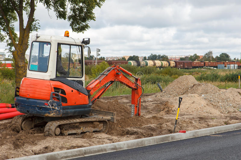 Excavator. An excavator in a road construction site stock images