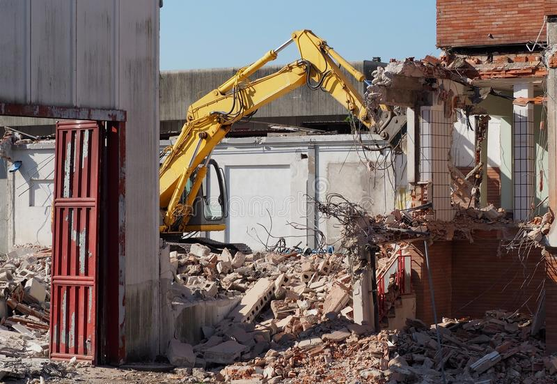 An excavator demolishes an industrial site for urban redevelopment in residential use. An excavator, among the rubbles, demolishes an industrial site for urban royalty free stock photography