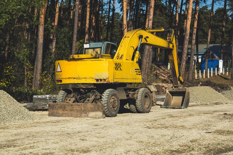 excavator at sandpit during earthmoving works. Yellow excavator on wheels stock photos