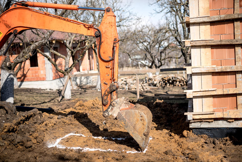 Excavator scoop on construction site, digging and loading dumper trucks. Excavator scoop on construction site, digging earth and loading dumper trucks royalty free stock photos