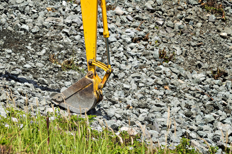 Excavator shovel digging rock. On constriction site stock photo