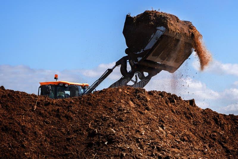 Excavator shovel working on a large heap of manure, organic fert royalty free stock photos