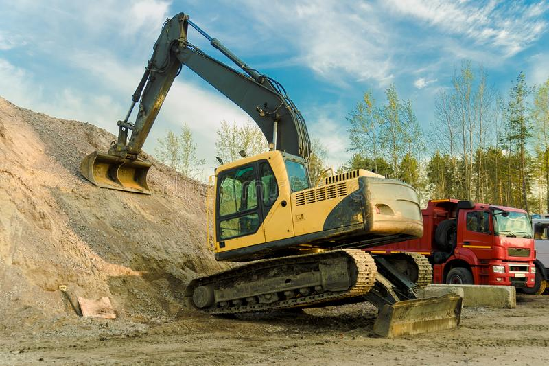 Excavator stands in the Parking lot after a hard day stock images
