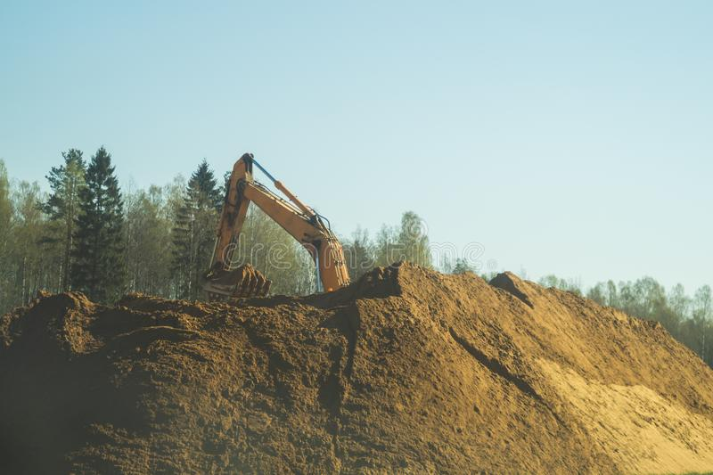 Excavator stands on the sand hill and digs the ground. part of construction earthmoving equipment royalty free stock image