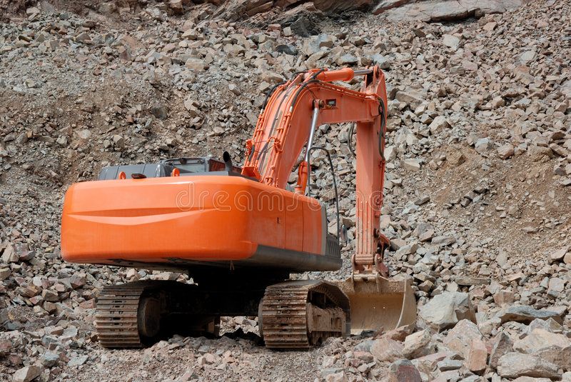 Excavator in a stone pit. Red excavator in a stone pit stock images