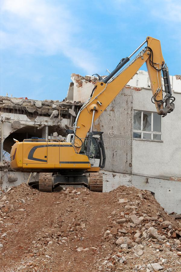 Excavator storms old house royalty free stock photos