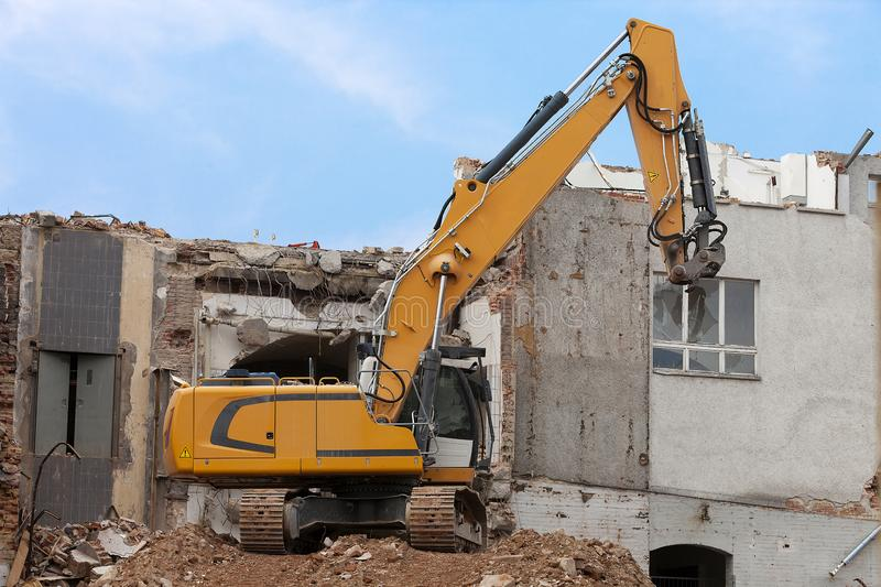 Excavator storms old house. For construction of new apartments royalty free stock photos
