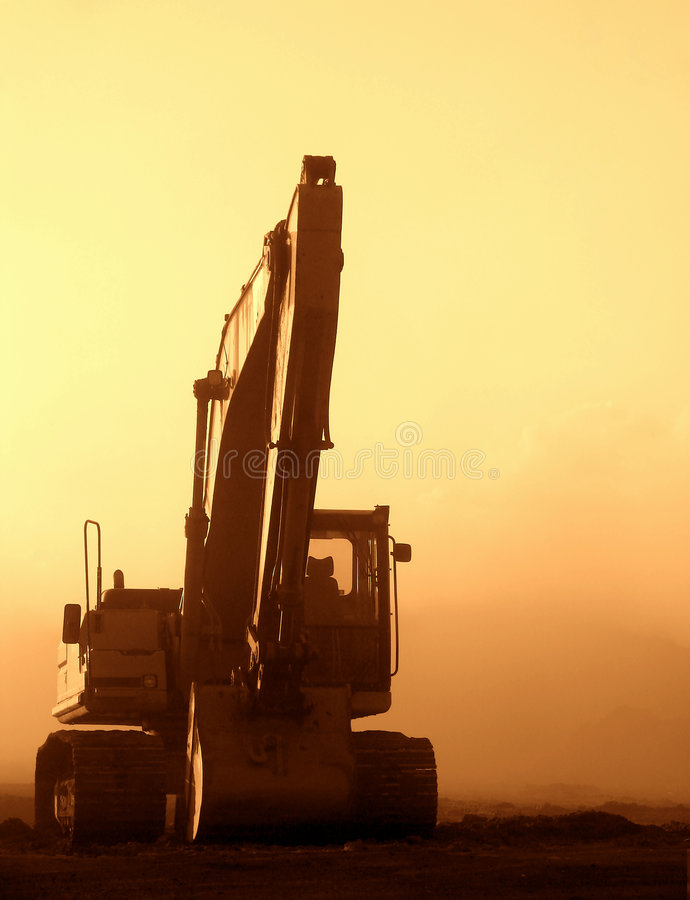 Excavator at Sunset on a Dusty Construction Site royalty free stock photo
