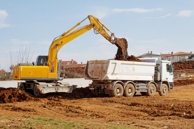 Excavator and tipper truck royalty free stock photo