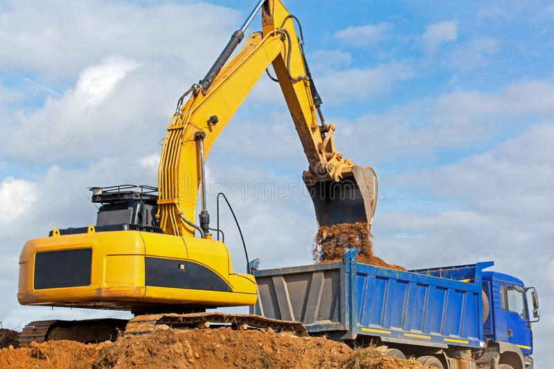 Excavator unloading sand into tipper truck royalty free stock image
