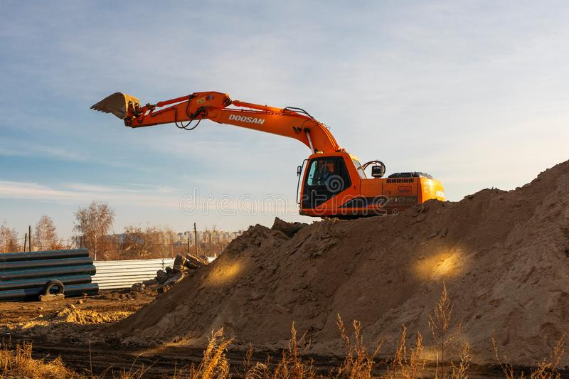 Excavator used for pipe laying works and house foundation. Doosan earth mover machine Russia, Omsk, 13.11.2019 stock image