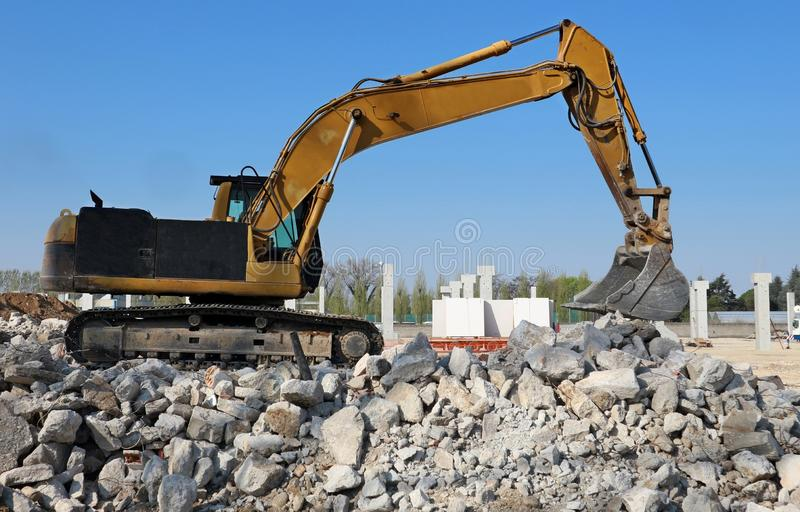 Excavator at work above a pile of debris in an industrial redevelopment area.  royalty free stock photos