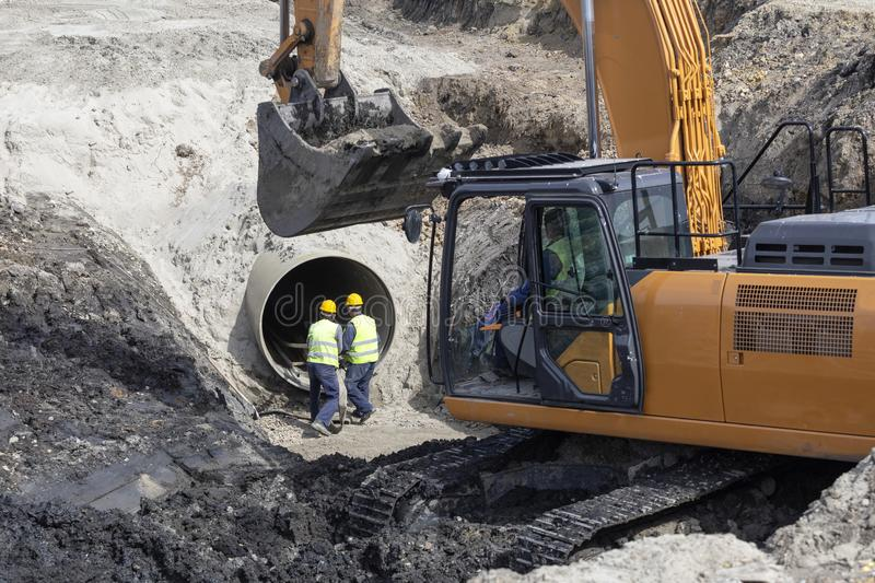 Excavator and workers making trench bed for new pipeline. Construction stock images