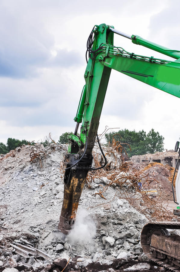 Excavator working at the demolition of an old industrial buildin. G stock photo