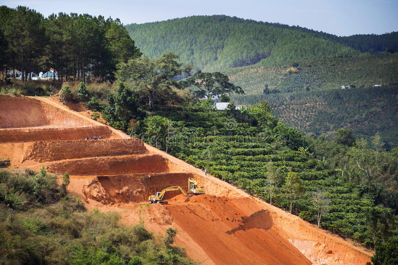 Excavators dig terraces for coffee beans plantations in Vietnam. Diggers excavate terraces for coffee beans plantations in Vietnam stock images