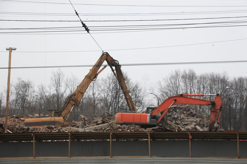 Excavators, dismantling the old building royalty free stock image