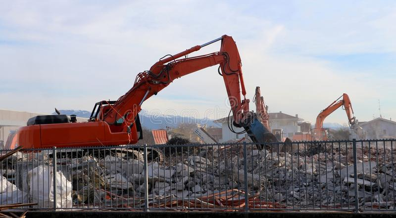 Excavators at work, between rubble and dust, for an urban redevelopment. In a construction site royalty free stock photography