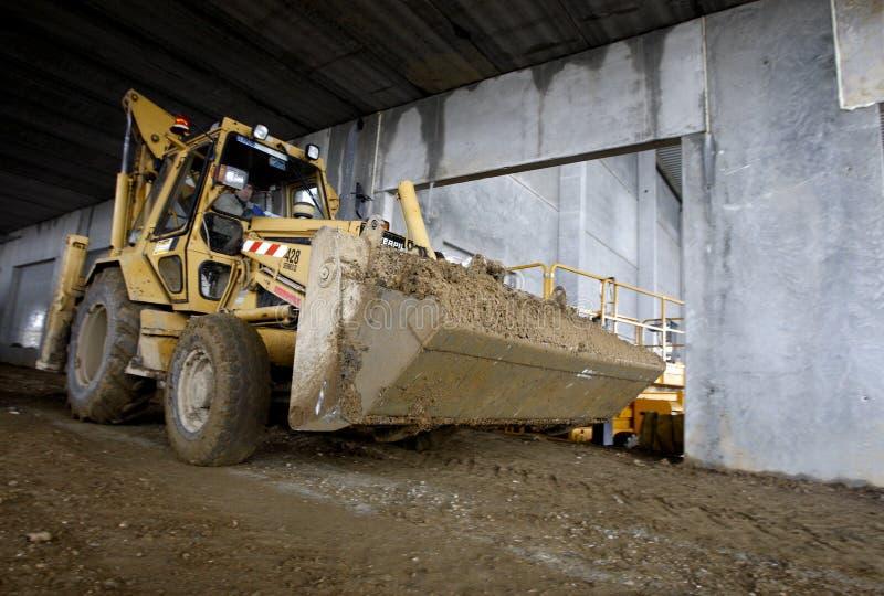 Excavatrice à l'intérieur de la construction industrielle en cours photos libres de droits