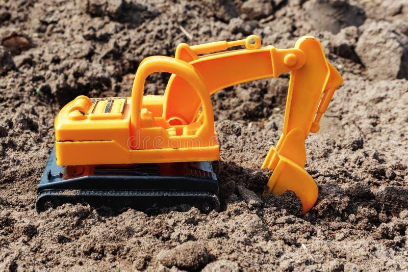 Excavatrice de jouet creusant la terre Le concept des travaux de terre images stock