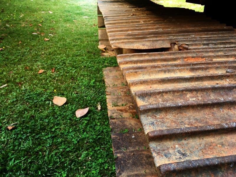 Excavatrice de pelle rétro sur le cadre rouillé de chenille sur le champ d'herbe dans le jardin image stock