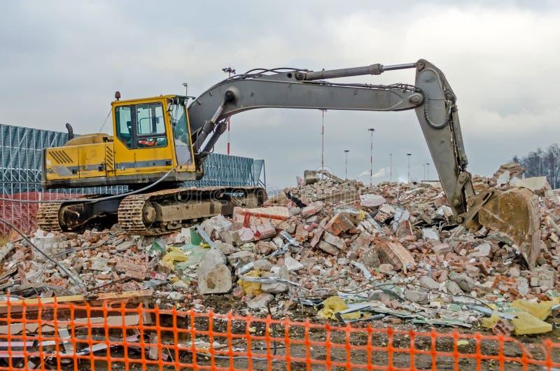 Excavatrice fonctionnant à la démolition d'un vieux bâtiment industriel image stock