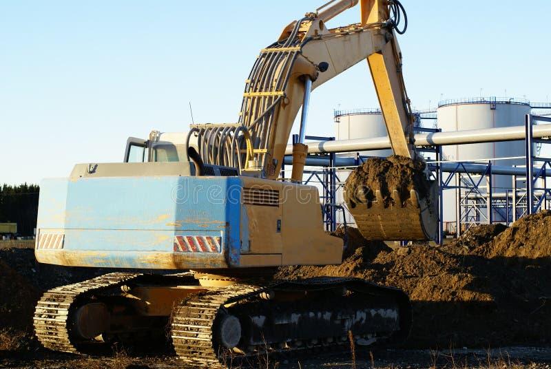 Excavatrice hydraulique au travail contre le ciel bleu photographie stock libre de droits