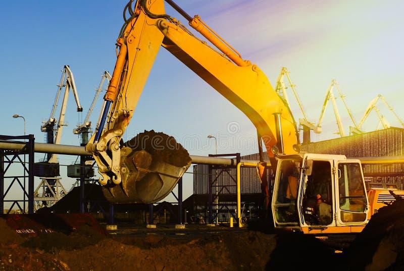 Excavatrice hydraulique au travail Seau et grues de pelle contre le bl photo stock