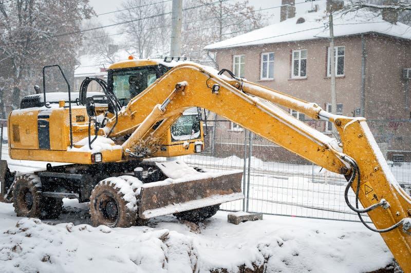 Excavatrice jaune couverte par la neige au chantier de construction d'hiver photographie stock